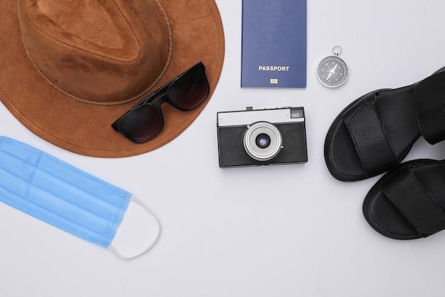 Podróżuj podczas pandemii covid-19. sandały, kapelusz, akcesoria podróżne i maska medyczna na białym tle. widok z góry