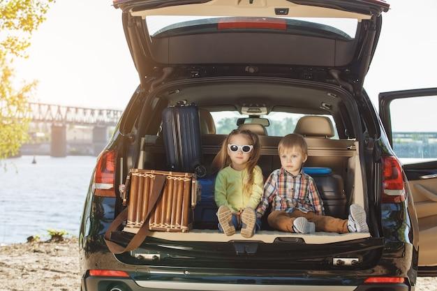Podróżuj samochodem z rodziną razem z bratem i siostrą siedzącymi w bagażniku