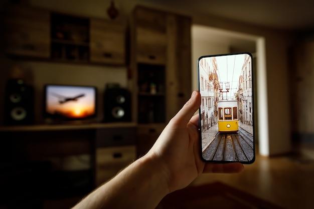 Podróżuj w domu. wycieczka online do lizbony w portugalii za pośrednictwem smartfona. legendarny żółty tramwaj na ekranie
