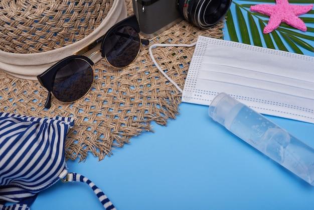 Podróżuj w notatkach z kwarantanny epidemicznej. widok z góry stołu z aparatem, kapeluszem, bikini, okularami przeciwsłonecznymi, maską na twarz. środki higieny osobistej i środki ochrony w tematyce turystycznej. ograniczenia