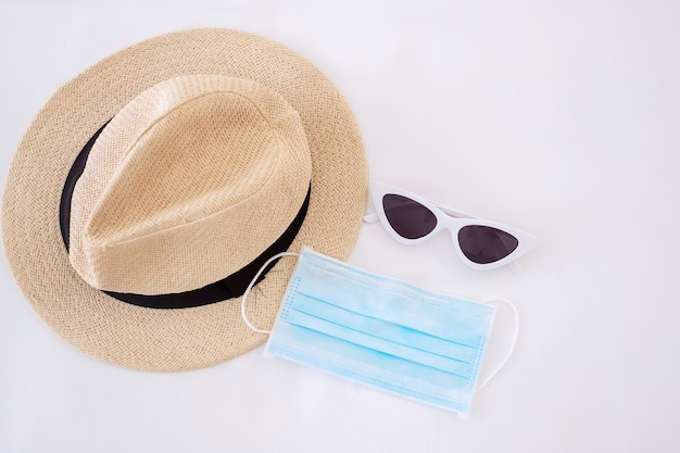 Podróżuj W Ramach Covid-19 I Nowych Normalnych Koncepcji. Medyczna Maska Na Twarz, Okulary Przeciwsłoneczne I Kapelusz Plażowy Na Białym łóżku, Zapobiegają Koronawirusowi Lub Chorobie Koronawirusa Premium Zdjęcia