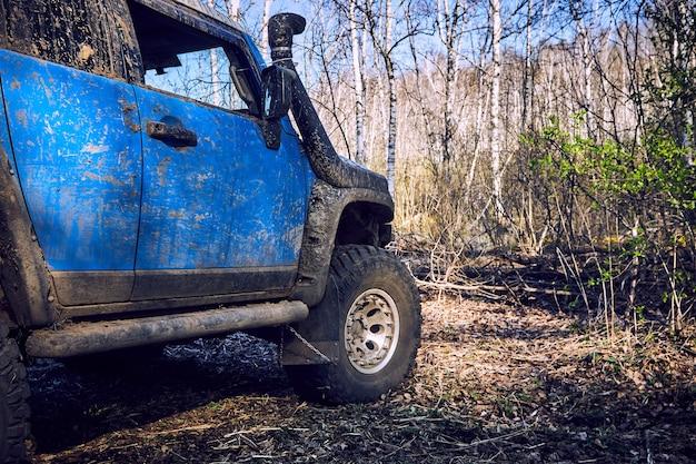 Podróżuj w terenie po leśnej drodze w niebieskim samochodzie 4x4. suv 4x4 jest cały brudny