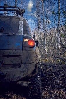 Podróżuj w terenie po leśnej drodze w niebieskim samochodzie 4x4. suv 4x4 wszystkie brudne cofa się ze ślepego zaułka