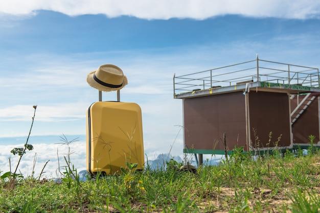 Podróżuj walizką z kapeluszem na charakter pięknej górskiej scenerii i mgły