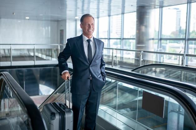Podróżuj wygodnie. radosny człowiek sukcesu w stylowym garniturze z nowoczesną walizką poruszającą się po schodach ruchomymi na lotnisko w godzinach popołudniowych