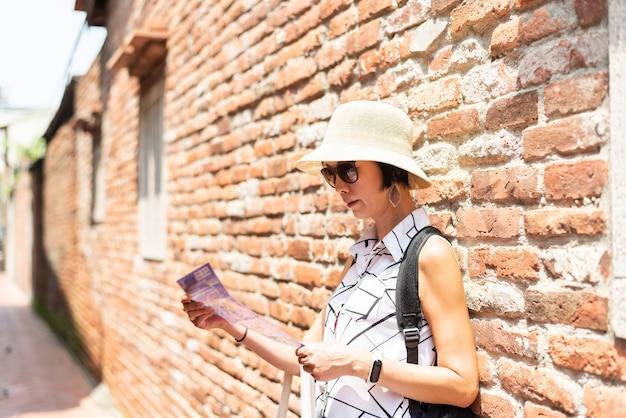 Podróżująca azjatka sprawdź mapę na starej ulicy w mieście lukang w hrabstwie changhua, tajwan, azja