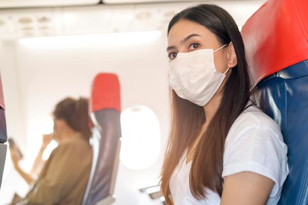 Podróżująca kobieta nosi maskę ochronną na pokładzie samolotu, podróżując w warunkach pandemii covid-19