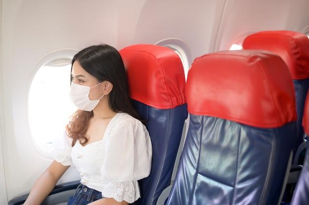 Podróżująca kobieta nosi maskę ochronną na pokładzie samolotu, podróżuje w czasie pandemii covid-19, podróże bezpieczeństwa, protokół zachowania dystansu społecznego