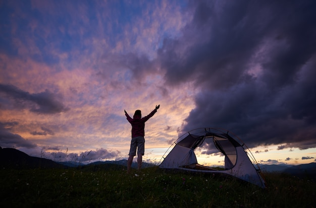 Podróżująca kobieta, podnosząca ręce, cieszy się widokiem cudownego świtu na górze