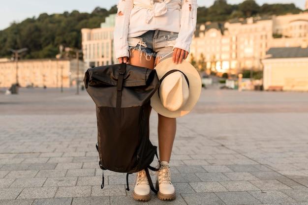 Podróżująca kobieta pozuje z kapeluszem i plecakiem