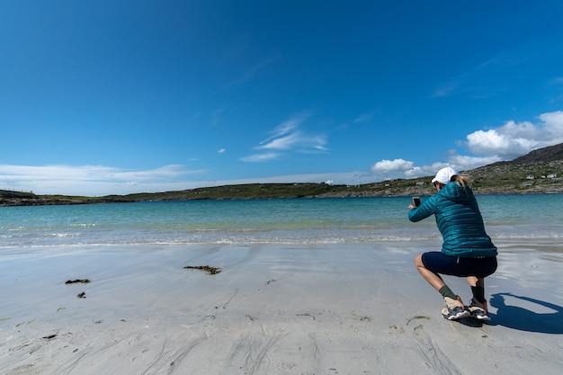 Podróżująca kobieta robi zdjęcie plaży telefonem komórkowym w dog's bay galway, irlandia