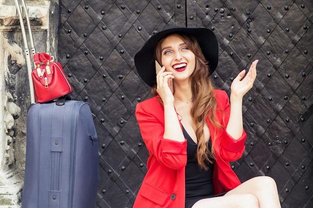 Podróżująca kobieta rozmawia na smartfonie z walizką w pobliżu starych drzwi na ulicy miasta.