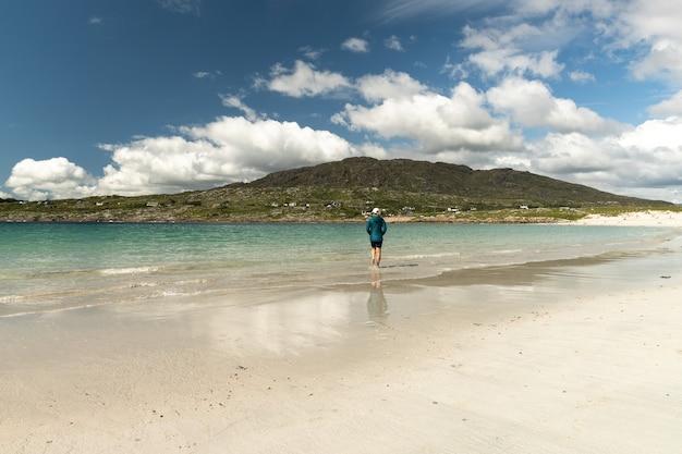 Podróżująca kobieta spacerująca wzdłuż białej, piaszczystej plaży i czystej wody w dog's bay galway, irlandia