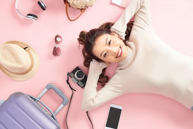 Podróżująca kobieta uśmiecha się radośnie i patrzy gdzieś leżąc na różowej podłodze