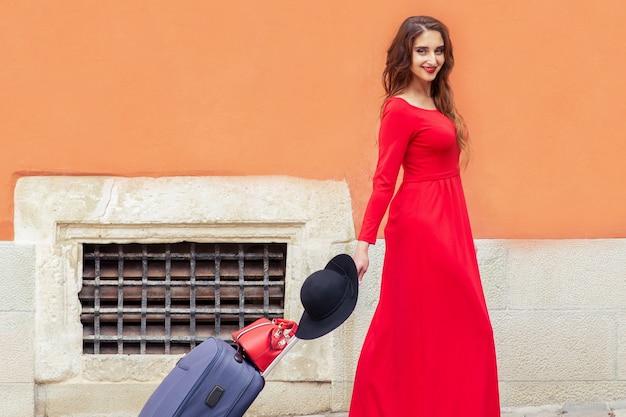 Podróżująca kobieta w czerwonej sukience długiej, ciągnąca walizkę na ulicy miasta.