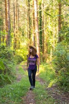 Podróżująca kobieta w kapeluszu i patrząca na leśne sosny