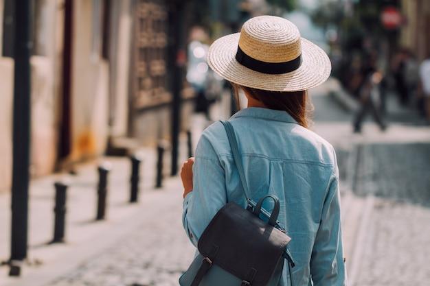 Podróżująca kobieta w kapeluszu iz plecakiem spaceruje ulicą europejskiego miasta. styl życia na wakacje i podróże. koncepcja podróży
