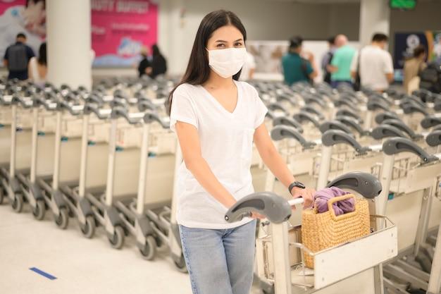 Podróżująca kobieta w masce ochronnej na lotnisku z bagażem na wózku, podróż w czasie pandemii covid-19, podróże bezpieczeństwa, protokół zachowania dystansu społecznego, nowa koncepcja normalnej podróży