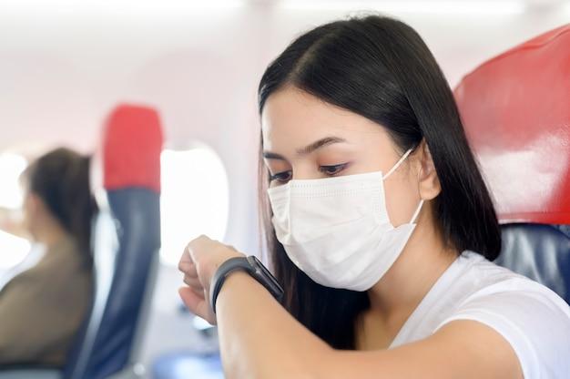 Podróżująca kobieta w masce ochronnej na pokładzie samolotu za pomocą inteligentnego zegarka, podróżująca pod pandemią covid-19