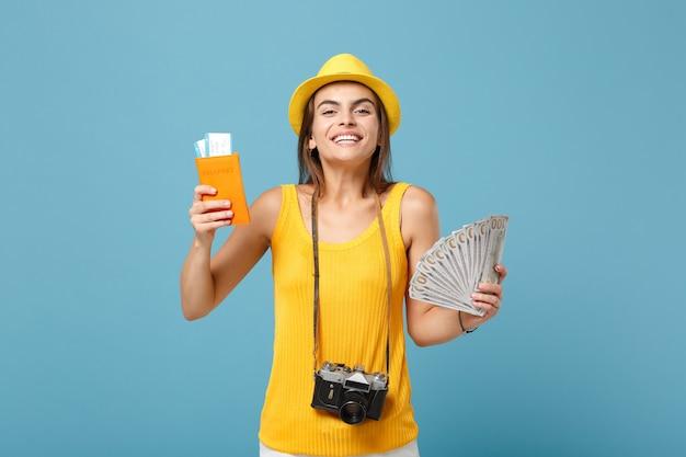 Podróżująca kobieta w żółtych codziennych ubraniach i kapeluszu, trzymająca bilety, kamera pieniędzy na niebiesko