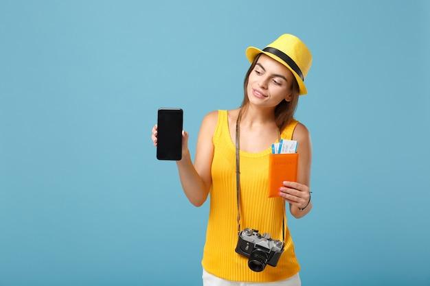Podróżująca kobieta w żółtych codziennych ubraniach i kapeluszu, trzymająca bilety, telefon komórkowy i aparat na niebiesko