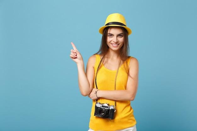 Podróżująca kobieta w żółtych letnich ubraniach i kapeluszu z aparatem fotograficznym na niebiesko