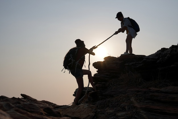 Podróżująca kobieta wyciąga ręce od przyjaciela do góry. pomysły na sukces, pracę zespołową i przywództwo.