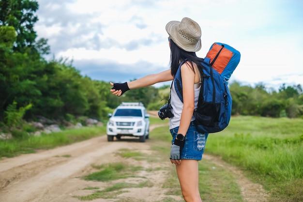 Podróżująca kobieta z azji jedzie autostopem w podróż do celu.