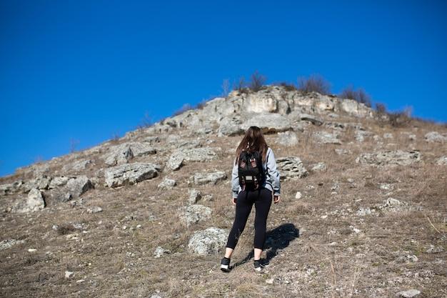 Podróżująca kobieta z plecakiem wspina się po stromym skalistym terenie z błękitnym niebem