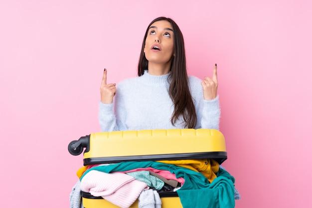 Podróżująca kobieta z walizką pełną ubrań na izolowanej różowej ścianie wskazująca palcem wskazującym to świetny pomysł