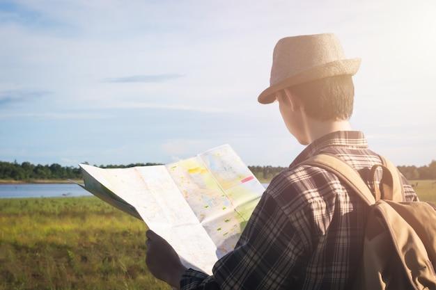 Podróżujący azjatykci młody męski turysta używa lokalną mapę z rocznika plecakiem przy jeziorną wsi naturą