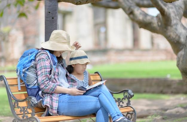 Podróżujący matka i córka rozmawiają i siedzą na krześle