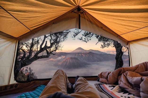 Podróżujący mężczyzna relaksujący się i podziwiający aktywny wulkan bromo wewnątrz namiotu rano w parku narodowym bromo tengger semeru, indonezja