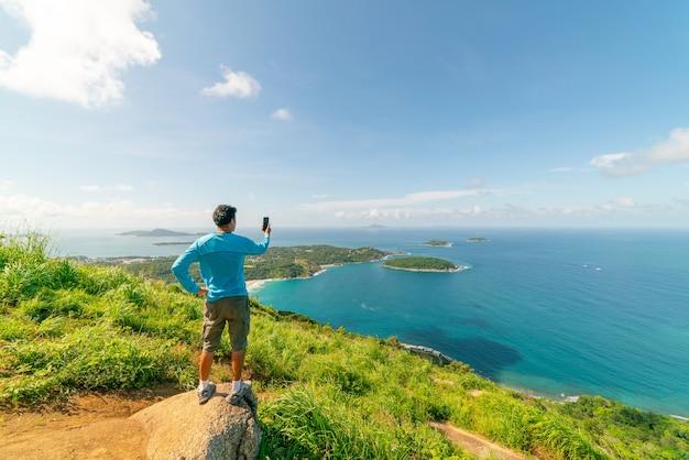 Podróżujący mężczyzna stojący na skale zrób zdjęcie lub nagraj widok krajobrazu z punktu widokowego phahindum, popularnego punktu widokowego w phuket tajlandia punkt widokowy, aby zobaczyć przylądek promthep plażę naiharn i plażę yanui niesamowity widok.