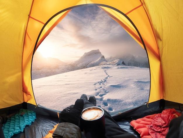 Podróżujący mężczyzna trzymający filiżankę kawy i cieszący się widokiem wschodu słońca na zaśnieżonej górze w żółtym namiocie