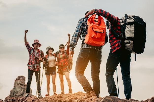 Podróżujący mężczyzna wspierający rannego przyjaciela wspina się po górach drużyną, która dotarła na szczyt