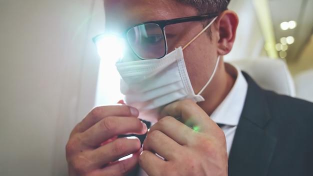 Podróżujący noszący maskę podczas podróży samolotem komercyjnym. pojęcie wpływu epidemii koronawirusa lub pandemii covid 19 na turystykę i działalność lotniczą.