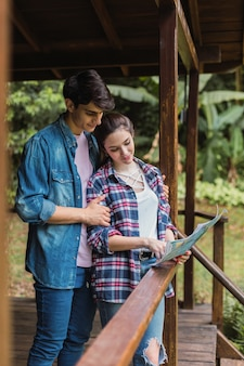 Podróżujący para patrząc na mapę na balkonie swojego pokoju hotelowego