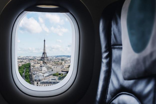 Podróżujący paryż, francja słynny punkt orientacyjny i cel podróży w europie. widok z lotu ptaka wieża eiffla przez okno samolotu