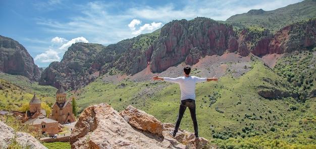 Podróżujący szczęśliwy człowiek stojący na wysokiej skale