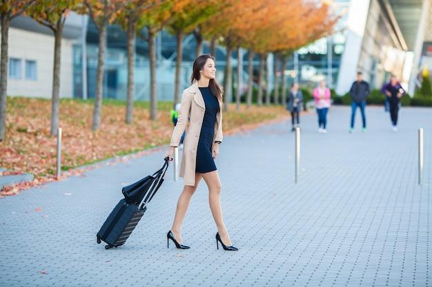 Podróżuje, biznesowa kobieta opowiada na smartphone na lotnisku podczas gdy chodzący z podręcznym bagażem na lotnisku iść brama, dziewczyna używa telefon komórkowego dla rozmowy