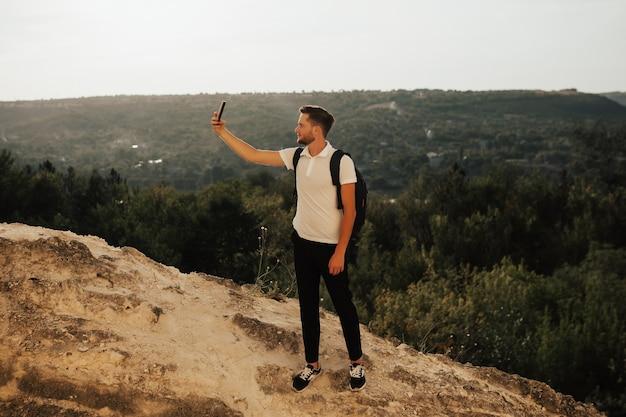 Podróżuje człowiek z plecakiem biorąc selfie na skalistej górze.