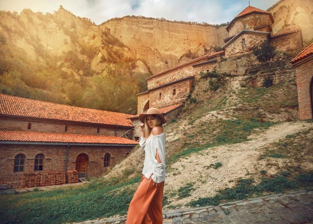 Podróżuje kobieta pozuje na tle gór i średniowiecznego monasteru.