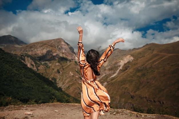 Podróżuje kobieta turysty pozuje na tle chmurnego nieba i gór.