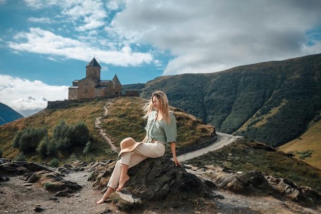 Podróżuje kobieta turysty pozuje na tle gór i średniowiecznego monasteru.
