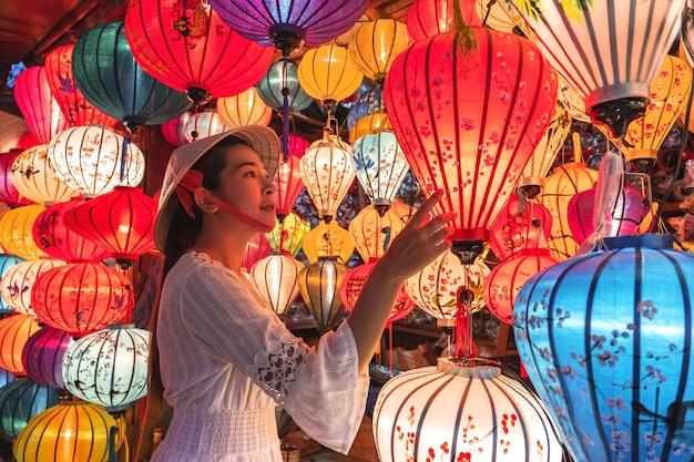 Podróżuje kobiety wybiera lampiony w hoi an, wietnam