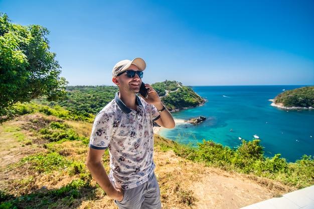 Podróżuje młody człowiek pozyci rozmowy telefon i widzii pięknego sceneria krajobrazu natury widok na rockowej górze w phuket thailand.