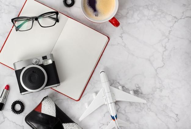 Podróżuje płaskich przedmioty na białym drewnianym stole z kopii przestrzenią. terminarz, szklanki, filiżanka kawy, aparat fotograficzny, kolczyki w uszach, krawat do włosów, grzebień i szminka przy stylowym marmurowym stole