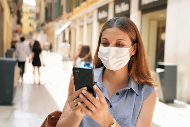 Podróżuje z zieloną przepustką. atrakcyjna kobieta oglądając jej telefon komórkowy na ulicy miasta. turystyka z koncepcją certyfikatu cyfrowego covid.