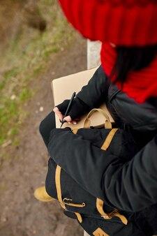 Podróży kobieta z czerwonym kapeluszu w czarnej kurtce pisać na notebooku, robić notatki, rysować szkic z widokiem na rzekę, lokalne podróże, zdrowie psychiczne. jesień, jesień